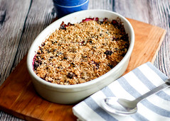 Close Up Food Photo of Homemade Berries Crumble in a Backing Tray on a Wooden Board