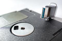 Nahaufnahme einer Floppy Diskette und eines USB-Sticks