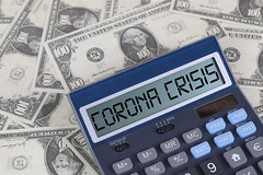 Corona Crisis text on calculator screen on the hundred dollar bills