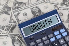 Growth text on calculator screen on the hundred dollar bills