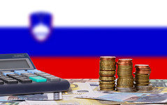 Calculator with money and coins in front of flag of Slovenia
