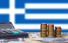 Calculator with money and coins in front of flag of Greece