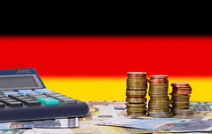 Calculator with money and coins in front of flag of Germany