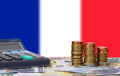 Calculator with money and coins in front of flag of France