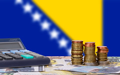 Calculator with money and coins in front of flag of Bosnia and Herzegovina