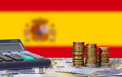 Calculator with money and coins in front of flag of Spain