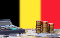 Calculator with money and coins in front of flag of Belgium