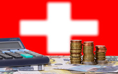 Calculator with money and coins in front of flag of Switzerland