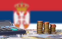 Calculator with money and coins in front of flag of Serbia