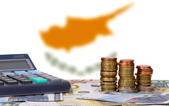 Calculator with money and coins in front of flag of Cyprus