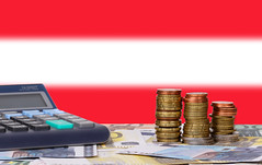 Calculator with money and coins in front of flag of Austria