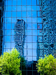 Reflections of Canary Wharf's new residential towers in the glass of an office at Millwall Dock