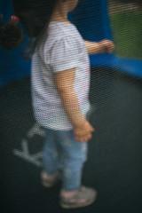 Little girl on trampoline.
