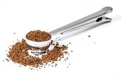 Messlöffel mit Pulverkaffee auf weißem Hintergrund