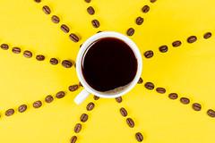 Eine Tasse schwarzer Kaffee auf gelbem Hintergrund mit Kaffeebohnen. Aufnahme von oben