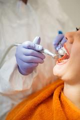 Dentist adjusting braces to patient.