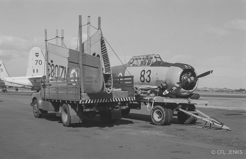 27 November 1975, RNZAF Harvard NZ1083 dismantled on trailer at Whenuapai after landing accident at Kaikohe. RAAF Neptunes A89-270 and A89-275 in background