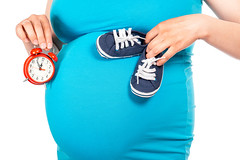 Beautiful small blue shoes at the pregnant woman's belly and red alarm in hand