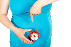 A pregnant woman points to her stomach and watch. The concept of waiting, time