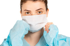 Close-up of a girl in a medical mask and dressing gown