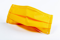 Yellow medical mask on a white background. Individual protection from respiratory diseases