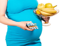 Young woman's holding blister packs of pills and fresh fruits. Concept receiving vitamins in pregnancy time