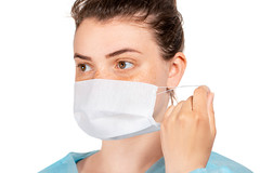 A nurse in a medical gown puts a disposable mask on her face