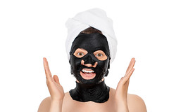 Girl with a black mask on her face to cleanse skin pores. The concept of care and beauty