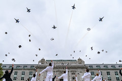 The Blue Angels fly over Bancroft Hall as midshipmen toss their covers.