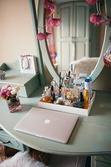 Macbook and perfumes on wooden table.