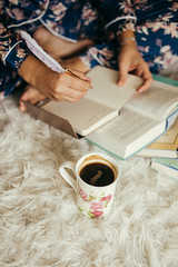 Woman  drinking coffee and writing in journal