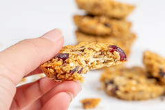 Close-up, a piece of oatmeal cookies with seeds and raisins in a woman's hand