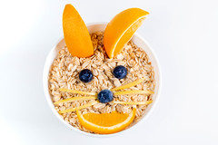 Top view, a bowl of oatmeal decorated with fresh fruit in the shape of a rabbit face