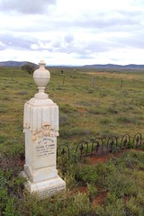 Flinders Ranges South Australia. Lone headstone for Coombe in the Wilson cemetery. Wilson is now a deserted ghost town. In the distance are some stone ruins.