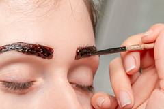 Master with a brush draws eyebrows with henna. Natural paint