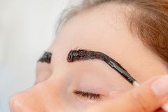 Close-up, henna staining a woman's eyebrows