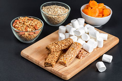Marshmallows, granola bars, oatmeal and dried apricots on a dark background