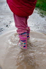 Photo of child splashing in puddle with rubber boots.