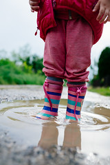 A little girl standing in the water.