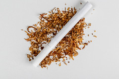 Top view, cigarette on and dry tobacco on white background