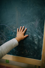 Little girl`s hand on chalkboard