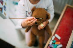 Little girl holding brush and teddy bear.