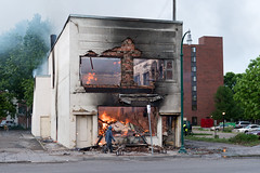 A man walks by a burning building on Thursday morning after a night of protests and rioting in Minneapolis, Minnesota