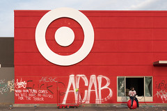 A man sits on a Target ball in front of the store on Thursday morning. The store was looted and graffitied after a night of protests in Minneapolis, Minnesota