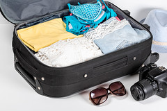 The concept of summer holidays and travel. Suitcase with clothes and camera on a white background
