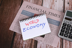 Financial Times newspaper with calculator and World Economy text on wooden table