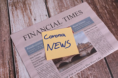 Financial Times newspaper with Corona News sticky note on wooden table