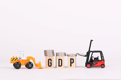 Forklift with pile of coins and GDP text