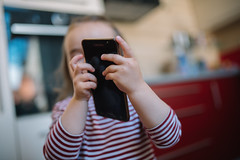 little girl looking at phone closeup.