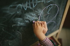 Woman and daughter writes on chalkboard. Arms closeup.